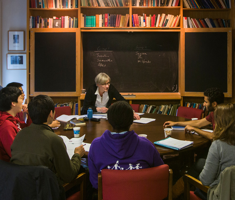 Philosophy professor sits at a table with her class of 6 students in a cozy room lined with book shelves