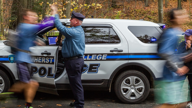 An Amherst College Police officer high-fives a student
