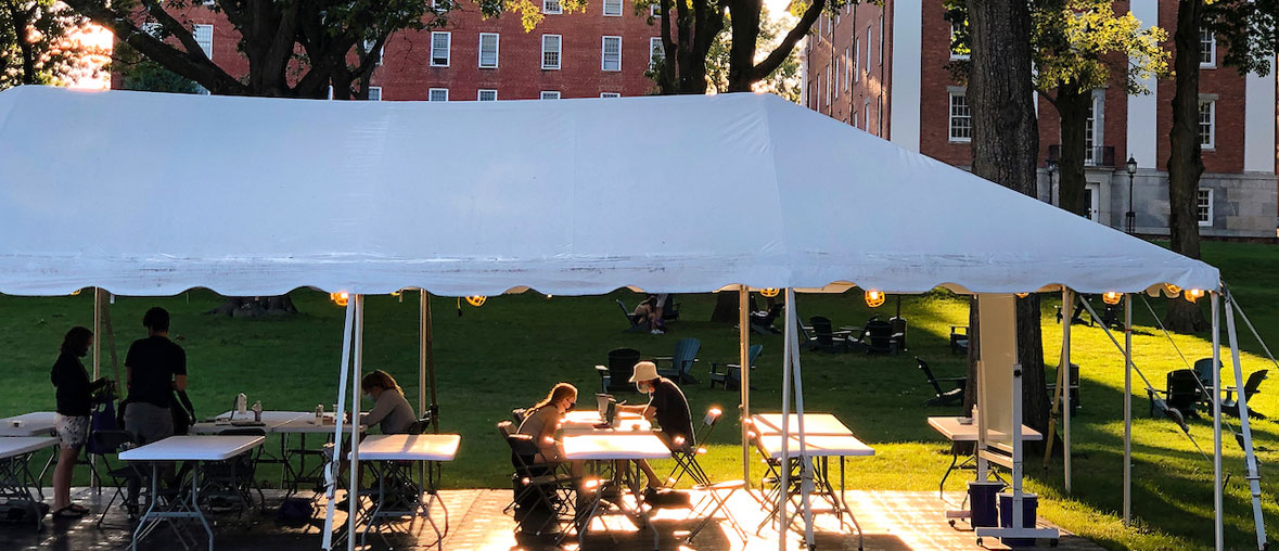 students wearing masks study outside under a tent together with sunlight streaming onto the quad