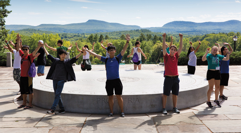 Students stand in a circle holding their hands, joined, up in the air, with a mountain range behind them