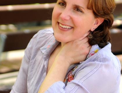 Closeup of Dawn Upshaw smiling, wearing a pale purple blouse, and holding her left hand to her neck