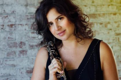 Closeup of Anat Cohen wearing a black blouse and holding her clarinet over her right shoulder
