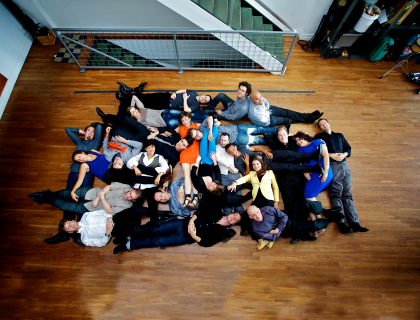 Overhead shot of members of the International Contemporary Ensemble lying down on a shiny wooden floor