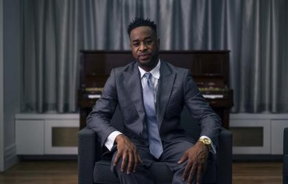 Damien Sneed seated in an armchair in front of a piano, wearing a suit and tie