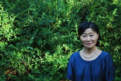 Chonghyo Shin standing in front of green foliage