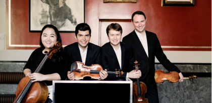 Calidore String Quartet posing with their instruments