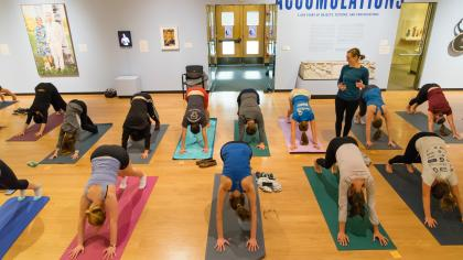 Two rows of people doing yoga on mats during a class in a Mead Art Museum gallery