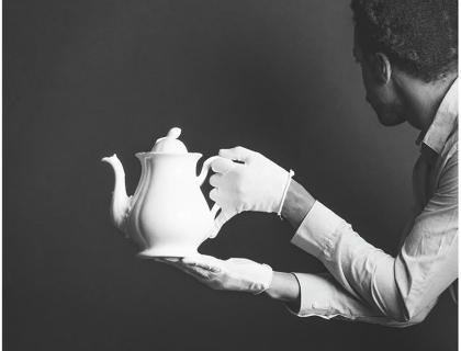 Black-and-white image of a Black male figure wearing white gloves, holding a teapot and looking away.