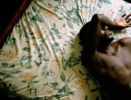 Overhead photograph of a shirtless black man lying on a bed with floral sheets, holding his right arm over his eyes