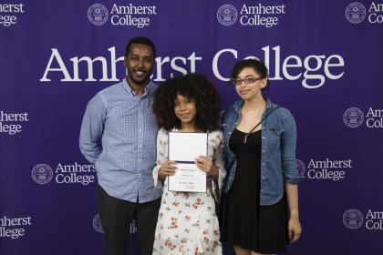 An award recipient and two others stand in front of an Amherst media backdrop