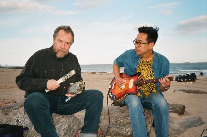 The two members of 75 Dollar Bill sitting on rocks on a beach, holding musical instruments