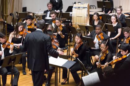 Members of the Amherst Symphony Orchestra playing onstage while Mark Lane Swanson conducts