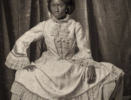 Black and white photograph of the artist in Victorian dress performing the role of Sarah Forbes Bonetta.