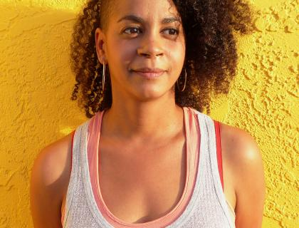 Aisha Sabatini Sloan wearing layered tank tops and hoop earrings, standing in front of a yellow wall