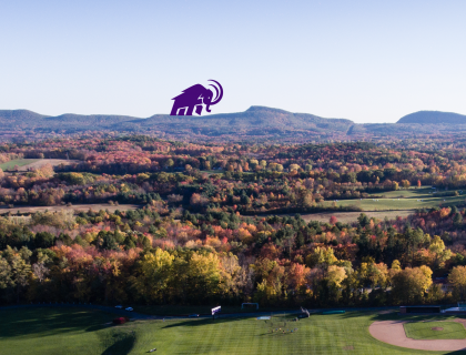 Western Massachestts landscape with foliage, mountains and a purple Mammoth logo in the distance