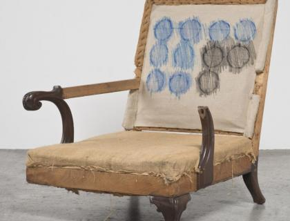 Sculpture of arm chair missing one leg and one arm; blue and black circle print on chair back.