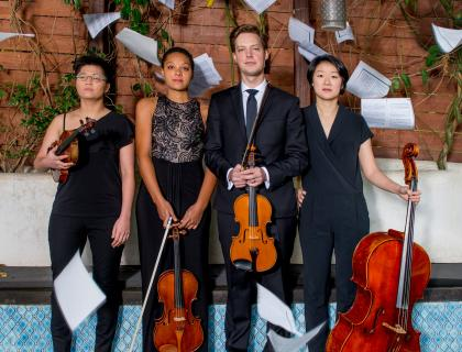 Argus Quartet standing with their instruments, with sheets of paper fluttering in the air around them