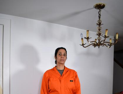 Image of a barefoot woman in an orange jumpsuit. A brown chandelier hangs from the ceiling and casts a shadow on a blank white wall.