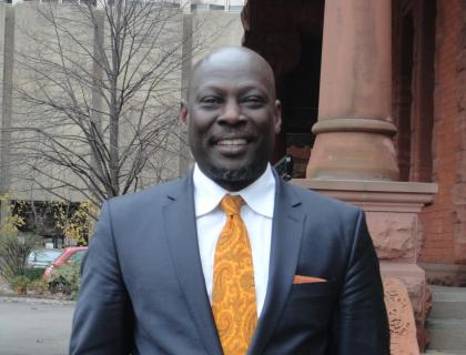 Closeup of Ato Quayson standing outdoors, wearing a suit and tie and smiling