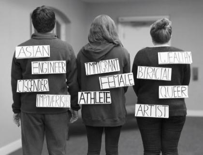 Image of the backs of three students displaying labels denoting race, sexuality, gender, class, and career