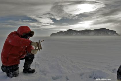 Davila research image showing a researcher wearing a read parka and kneeling down amid a snowy landscape, under a cloudy sky