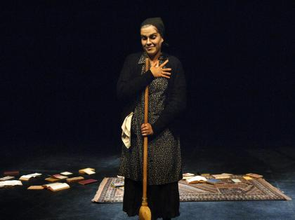 A woman standing on a dark stage holding a broom, with a rug and books scattered behind her