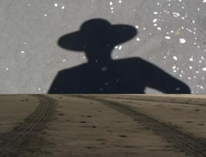 Illustration showing the shadow of a person wearing a wide-brimmed hat, beyond a landscape of dirt with tire tracks