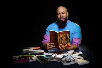 Photo of Dr. Callier sitting behind a pile of books