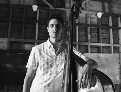 Black-and-white photo of Noah Garabedian standing with his arm around his bass