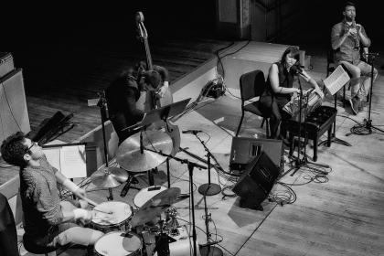 Black-and-white overhead photo of the Elder Ones and Amirtha Kidambi playing instruments on stage