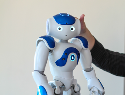 Robot standing on table with supportive hand behind it