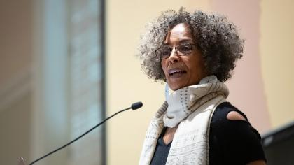 Photo of Fania Davis speaking in front of a podium microphone