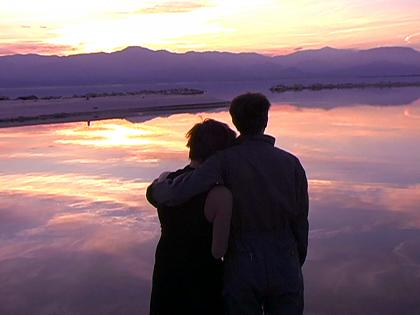 Image of one person with their arm around another as they look out over a body of water toward mountains at either sunrise or sunset