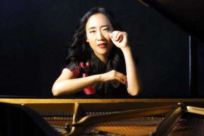 Portrait of Helen Sung sitting at an open piano