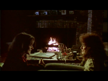 """Film still from """"Girlfriends,"""" showing two women facing each other and smiling as they sit on a couch in front of a fireplace"""