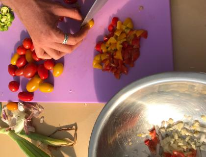 Hand chopping cherry tomatoes on a cutting board with a bowl of garlic nearby.