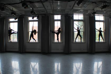 Five dancers posing in the windows of a studio