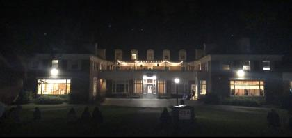 Image shows the Valentine Balcony lit up by string lights at night, some students sitting in the grass on the quad looking at the balcony where music is being played.