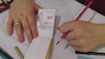 A pair of hands on a tabletop, holding a pink colored pencil and a hand-drawn flipbook