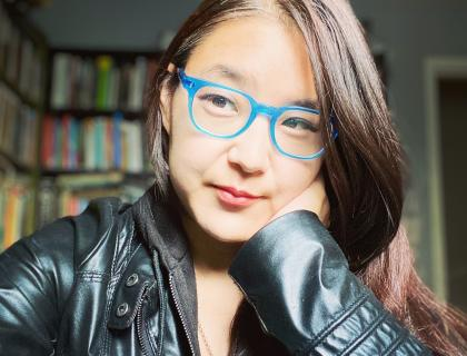 Janice Lee wearing a black leather jacket and blue-framed eyeglasses. Bookcases and part of a doorframe are visible in the room behind her.