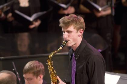 Closeup of Zach Yanes '17 playing the saxophone on stage in front of other musicians