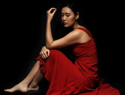 Jihye Lee, seated and barefoot, wearing a red dress