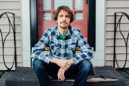 Joseph Scapellato seated on the front steps of a house, wearing a plaid shirt and blue jeans
