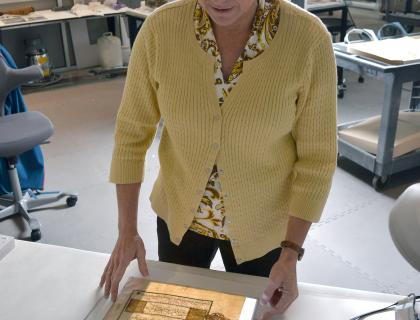 Julia Ream, standing at a table and examining a document under a light
