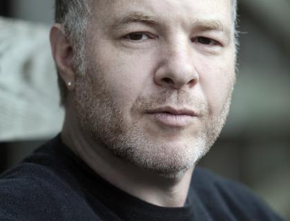 this is a photo of Jackson Katz.  He is a white man with a shirt few day growth beard, with brown hair with grey.  he is staring at the camera, wearing a serious expression. he is wearing a black shirt and the background is blurry.