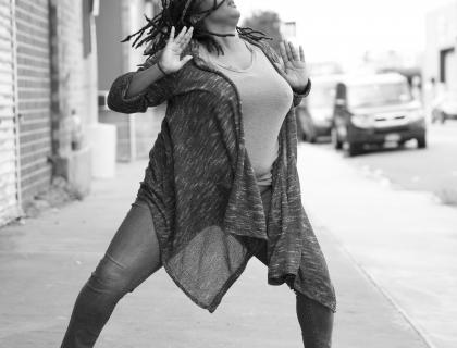 Black-and-white photo of Kayla Hamilton dancing on a city street