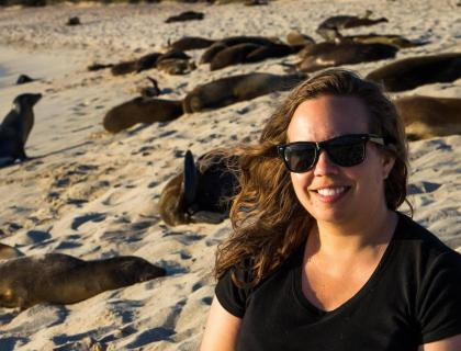 Sarah Knutie on a beach, with seals basking in the sand behind her