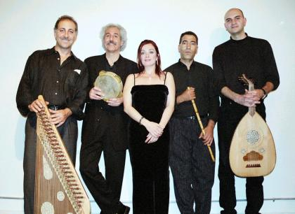 Five members of Layaali, dressed in black and holding musical instruments