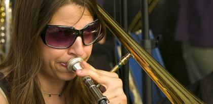 Closeup photo of Sara Jacovino wearing sunglasses and blowing into a trombone