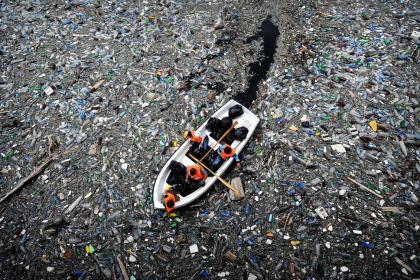 Boat with people collecting plastic from polluted ocean